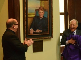 SHC President Dr. Christopher Puto, right, and Fr. Mark Mossa, S.J., at left, react at the unveiling of a portrait of the Rev. William J. Rewak S.J. The unveiling celebrated the naming of the Rotunda in honor of Rev. Rewak. (photo: Samm Brown)